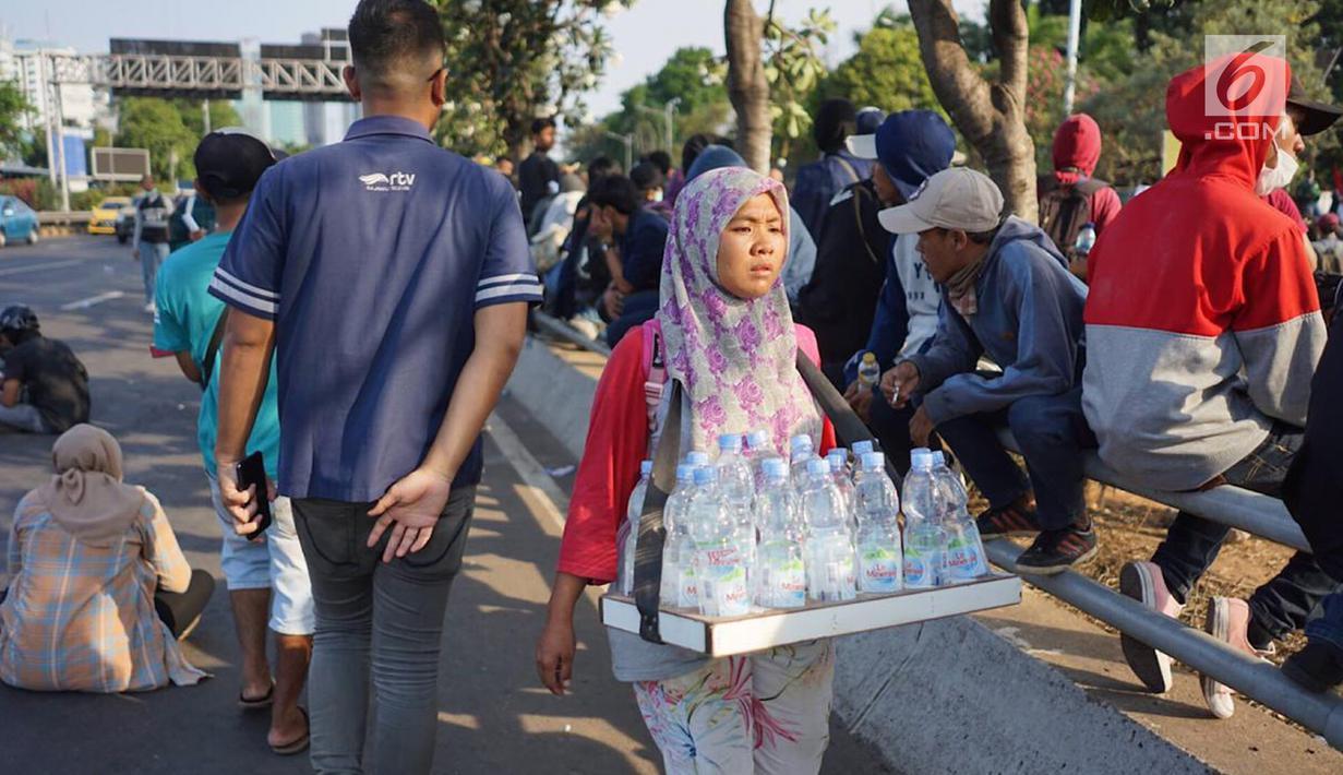 Seorang pedagang minum berjualan di jalan tol dalam kota yang berada di depan Gedung DPR RI, Jakarta, Senin (30/9/2019). Adanya aksi unjuk rasa di sekitar lokasi dimanfaatkan para pedagang asongan untuk mencari rezeki. (Liputan6.com/Immanuel Antonius)