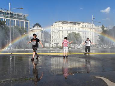 Anak-anak menyejukkan diri di dekat semprotan air di Schwarzenbergplatz di Wina, Austria (28/7/2020). Suhu tertinggi di Wina mencapai angka 37,2 derajat Celsius pada Selasa (28/7). (Xinhua/Guo Chen)