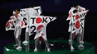 Penari membentangkan bendera berlogo Olimpiade Tokyo 2020 saat acara penutupan Olimpiade Rio 2016 di Stadion  Maracana, Rio de Janeiro, (22/8/2016). (AFP/Greg Baker)