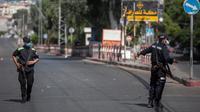 Polisi Hamas Palestina mengenakan masker berjaga di sebuah jalan saat pemberlakukan lockdown total selama 48 jam di Jalur Gaza, Selasa (25/8/2020). Lockdown dan jam malam diberlakukan menyusul terkonfirmasinya kasus Covid-19 pertama kalinya di sebuah kamp pengungsian. (AP Photo/Khalil Hamra)