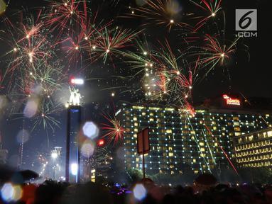 Kembang api menghiasi malam pergantian tahun baru 2019 di kawasan Bundaran HI, Jakarta, Selasa (1/1). Hujan yang mengguyur Jakarta tidak menyurutkan warga menikmati kembang api tahun baru. (Liputan6.com/Angga Yuniar)