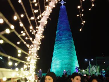 Orang-orang berkumpul di sekitar Pohon Natal raksasa yang terbuat dari botol plastik di kota Chekka, Lebanon, 15 Desember 2019. Sebanyak 129 ribu botol plastik ditata untuk menjadi pohon Natal setinggi 28.5 meter.  (Ibrahim CHALHOUB/AFP)