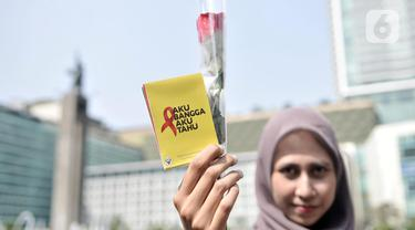 Seorang wanita menunjukkan bunga mawar dan buku panduan saat peringatan Hari AIDS Sedunia di Bundaran HI, Jakarta, Minggu (1/12/2019). Kegiatan ini bertujuan mengedukasi masyarakat tentang penyakit AIDS dan mengajak untuk peduli serta tidak menjauhkan penderita AIDS. (merdeka.com/Iqbal S. Nugroho)
