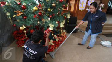 Petugas GO-CLEAN membersihkan pohon natal di GPIB Effatha di kawasan Melawai Jakarta Selatan, Rabu (21/12). Kegiatan ini merupakan rangkaian dari program #NatalanNyaman Bersama GO-CLEAN. (Liputan6.com/Fery Pradolo)