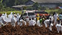 Pekerja menguburkan jenazah korban virus corona COVID-19 di TPU Pedurenan, Bekasi, Jawa Barat, Selasa (7/7/2021). Indonesia memperluas pembatasan untuk memerangi gelombang virus corona COVID-19 yang mematikan. (REZAS/AFP)