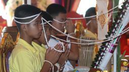 Anggota tim sepak bola remaja Thailand berdoa saat mengikuti ritual di Distrik Mae Sai, Chiang Rai, Kamis (19/7). Ritual dilakukan setelah 12 remaja Thailand yang sebelumnya terjebak di dalam gua berhasil diselamatkan. (AP Photo/Sakchai Lalit)