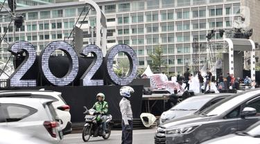 Kendaraan melintasi panggung hiburan yang disiapkan untuk menyambut malam pergantian tahun di Bundaran HI, Jakarta, Selasa (31/12/2019). Panggung megah disiapkan untuk memeriahkan Car Free Night dan pergantian tahun baru 2020 dengan menghadirkan sejumlah artis papan atas. (merdeka.com/Iqbal Nugroho)