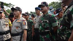 Panglima TNI Marsekal Hadi Tjahjanto (kanan) dan Kapolri Jenderal Tito Karnavian menghadiri apel pengamanan Pemilu 2019 di Bogor, Jawa Barat, Rabu (10/4). Panglima TNI dan Kapolri mengecek langsung kesiapan dan perlengkapan personel untuk mengamankan Pemilu 2019. (ADEK BERRY/AFP)
