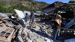 Orang-orang membersihkan puing-puing dari bangunan rumah yang rusak di Menggala, Lombok Utara, Rabu (8/8). Laporan terakhir mengatakan, gempa Lombok telah memakan 105 korban jiwa, dan lebih 70.000 orang kehilangan tempat tinggal. (AFP/ADEK BERRY)