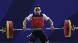 Lifter Eko Yuli melakukan angkatan saat SEA Games 2019 cabang angkat besi nomor 61 kg di Stadion Rizal Memorial, Manila, Minggu (1/12). Dirinya meraih emas dengan total angkatan 309 kg. (Bola.com/M Iqbal Ichsan)