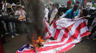 Massa aksi bela Palestina membakar bendera Amerika Serikat (AS) saat berunjuk rasa di depan Kedubes AS, Jakarta, Senin (11/12). Massa memprotes kebijakan Presiden Donald Trump yang mengakui Yerusalem sebagai Ibu Kota Israel. (Liputan6.com/Faizal Fanani)