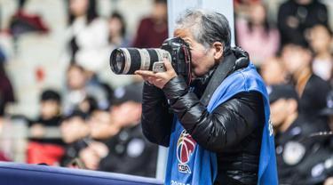 Fotografer Hong Nanli mengambil gambar saat pertandingan bola basket di Shanghai (16/1). Hong Nanli 79 tahun memulai karirnya sebagai fotografer sejak 1979, ia juga merupakan fotografer olah raga tertua di China. (AFP Photo/China Out)