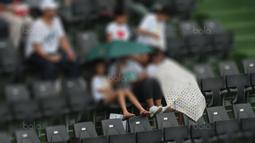Perilaku Orangtua berimbas ke anak-anak saat mengankat kaki diatas sandaran kursi pada laga Piala Davis 2018 grup dua Asia/Oceania di Senayan, Jakarta, Sabtu (3/2/2018). (Bola.com/Nick Hanoatubun)