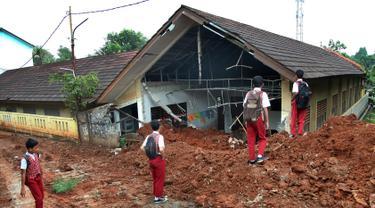 Murid melihat kondisi kelas SDN Bambu Apus 1 usai tertimpa truk pengangkut tanah proyek Tol Cinere-Serpong di Kelurahan Bambu Apus, Kecamatan Pamulang, Tangerang Selatan, Senin (14/1). Kejadian tersebut terjadi Minggu (13/1). (Merdeka.com/Arie Basuki)