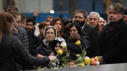Keluarga korban membawa bunga mawar dalam peringatan 25 tahun serangan bom truk di WTC, New York City, Amerika Serikat, Senin (26/2). Dalam serangan saat itu enam orang terbunuh dan lebih dari 1.000 orang terluka. (Spencer Platt/Getty Images/AFP)