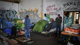 Pria muslim melakukan salat di gimnasium yang ditempati migran di lycee Jeanne-Bernard di Saint-Herblain, Prancis (28/3). Sebuah keputusan pengadilan 28 Maret 2019, menyusul  permintaan  keuskupan, pemilik situs, untuk mengusir para migran yang menempati gymnasium.  (AFP Photo/Loic Venance)