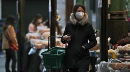 Seorang perempuan mengenakan masker saat berbelanja di Borough Market di London selatan selama penguncian nasional (lockdown) ketiga Inggris, Selasa (12/1/2021). Borough Market menjadi tempat pertama yang mewajibkan pemakaian masker di luar ruangan. (AP Photo/Alastair Grant)