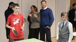 Pangeran Harry dan tunangannya Meghan Markle menyaksikan anak-anak bermain tenis meja saat berkunjung ke Star Hub, sebuah komunitas dan pusat rekreasi di Cardiff, Wales, (18/1). (AFP Photo/Pool/Geoff Pugh)