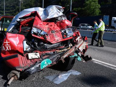 Taksi yang hancur terlihat setelah tabrakan dengan bus di Hong Kong (30/11). Lima orang tewas dan 32 luka-luka setelah akibat kecelakaan tersebut. (AFP Photo/Anthony Wallace)