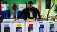 Petugas Kelompok Penyelenggara Pemungutan Suara (KPPS) berkostum superhero Batman menjaga kotak suara Pemilu 2019 di sebuah TPS di Surabaya, Jawa Timur, Rabu (17/4). Petugas KPPS rela berdandan ala superhero demi mengajak dan menarik pemilih agar mau datang ke TPS. (Juni Kriswanto/AFP)