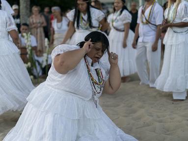 Seorang penganut kepercayaan Afro-Brasil menari memberi penghormatan kepada Yemenja sang Dewi Laut, ketika menyambut tahun baru di Pantai Copacabana di Rio de Janeiro (29/12/2019). Dalam kepercayaan Afro-Brasil, Yemanja diyakini sebagai representasi dewi laut yang cantik jelita. (AFP/Mauro Pimentel)