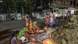 Warga bersiap di dekat Holika untuk melakukan ritual, Ahmedabad, India, Minggu (12/3). Bagi warga setempat Holika melambangkan kemenangan kebaikan atas kejahatan. (AFP PHOTO / SAM PANTHAKY)