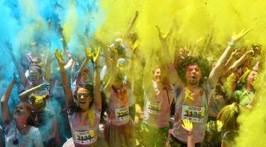 Peserta lomba bergembira saat disiram bubuk warna-warni saat mengikuti Kyiv Color Run di Kiev, Ukraina, Minggu (10/6). The Color Run diluncurkan dan diselenggarakan pertama kali pada Januari 2012 di Amerika Serikat. (AFP PHOTO/Sergei SUPINSKY)