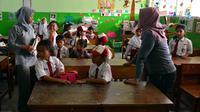 Sejumlah orang tua menemani anaknya masuk ke dalam kelas di hari pertama masuk sekolah di SDN 03, Pesanggrahan, Jakarta Selatan, Senin (16/7). Hari ini merupakan hari pertama masuk sekolah untuk tahun ajaran 2018-2019. (Merdeka.com/Arie Basuki)