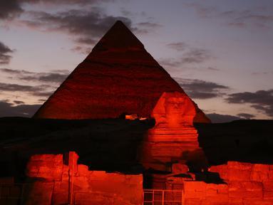 Patung Sphinx dan piramida berwarna merah saat pertunjukan cahaya dan suara di Giza, Mesir, Kamis (23/1/2020). Pertunjukan tersebut digelar sebagai bagian dari perayaan Tahun Baru Imlek. (Xinhua/Ahmed Gomaa)