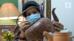 Perajin batik lukis ketel Nova Muhidir menyelesaikan lukisan batik di Studio Daroolang, Bintara, Tangerang Selatan, Banten, Rabu (2/12/2020). Lukisan ketel batik jadul khas nusantara di teko tempat air minum tersebut dijual dengan harga Rp 150 ribu hingga Rp 2,5 juta. (merdeka.com/Dwi Narwoko)