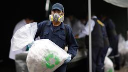 Pekerja memindahkan kokain yang siap dimusnahkan di markas polisi di Lima, Peru, (7/6). Polisi mengatakan mereka akan membakar sekitar 20 ton narkoba, termasuk kokain, mariyuana, opium dan heroin yang telah disita. (AP Photo/Martin Mejia)