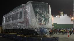 Pekerja dibantu alat berat menarik gerbong kereta ringan/Light Rail Transit (LRT) di Pelabuhan Car Terminal, Tanjung Priok, Jakarta, Jumat (13/4). Gerbong ini akan langsung diangkut menuju Dipo LRt di Kelapa Gading.  (Merdeka.com/Imam Buhori)