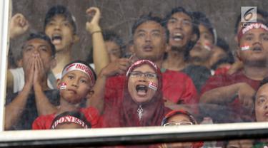 Suportermeluapkan ekspresi saat menyaksikan laga Timnas Indonesia U-19 melawan Jepang U-19 pada perempat final Piala AFC U-19 2018 di Stadion GBK, Jakarta, Minggu (28/10). Indonesia kalah 0-2.