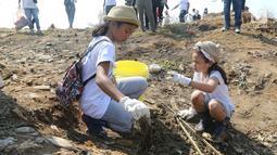 Dua anak membersihkan sampah di pantai timur ancol, Jakarta, Minggu (18/8/2019).  Gerakan Menghadap Laut 2.0 akan digelar serentak di lebih dari 100 titik lokasi di seluruh Indonesia. (Liputan6.com/Herman Zakharia)