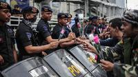 Peserta aksi yang tergabung dalam komunitas Spartan Nusantara membagikan bunga kepada Brimob di sekitar Gedung Bawaslu, Jakarta, Minggu (26/5/2019). Aksi tersebut sebagai bentuk terima kasih kepada TNI/Polri karena setia dan menjaga keamanan NKRI terkait sengketa pemilu. (Liputan6.com/Faizal Fanani)