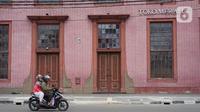 Pengendara motor melintas di kawasan wisata Kota Tua yang sepi dari aktivitas di Jakarta, Selasa (26/5/2020). Adanya program PSBB menyebabkan kawasan yang biasanya selalu ramai saat libur tersebut menjadi sepi dari pengunjung di hari kedua pascalebaran. (Liputan6.com/Immanuel Antonius)