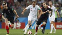 Striker Inggris, Harry Kane, berusaha melewati pemain Kroasia pada laga semifinal Piala Dunia di Stadion Luzhniki, Rabu (11/7/2018). Kroasia menang 2-1 atas Inggris. (AP/Alastair Grant)