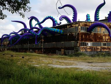 """Sebuah patung karet berjudul """"Sea Monsters HERE"""" menghiasi gudang berkarat Building 61 di Navy Yard di Philadelphia, Selasa (9/10). Instalasi buatan seniman Inggris Filthy Luker dan Pedro Estrellas ini ditampilkan hingga 16 November 2018. (AP/Matt Rourke)"""