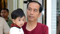 Presiden Jokowi sambil menggendong sang cucu, Jan Ethes menikmati libur akhir pekan di Mall Paragon, Solo, Jumat (30/3). Libur panjang akhir pekan ini dimanfaatkan Jokowi untuk berkumpul bersama keluarganya. (Liputan6.com/Pool/Kris-Biro Pers Setpres)
