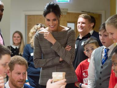 Pangeran Harry dan Meghan Markle melihat anak-anak bermain Jenga saat berkunjung ke sebuah komunitas dan pusat bermain di Cardiff, Wales, (18/1). Pasangan ini menghabiskan waktu ke Wales dengan mengunjungi komunitas tersebut. (Geoff Pugh/Pool via AP)