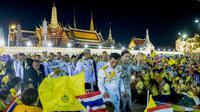 Raja Thailand Maha Vajiralongkorn (tengah kiri) dan Ratu Suthida (tengah kanan), melambaikan tangan ke arah para demonstran di Bangkok, Thailand, Minggu, 1 November 2020. (AP)