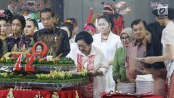 Ketum PDIP Megawati Soekarnoputri memotong tumpeng pada HUT ke-72 didampingi Presiden Joko Widodo serta Wapres Jusuf Kalla di Grand Sahid Jakarta, Rabu (23/1). Sejumlah menteri Kabinet Gotong Royong hadir dalam acara tersebut. (Liputan6.com/Angga Yuniar)