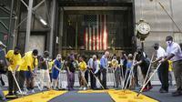 Walikota New York, Bill de Blasio, yang mengenakan masker oranye, berpartisipasi dalam melukis mural Black Lives Matter di Fifth Avenue di depan Trump Tower, New York, AS Kamis (9/7/2020) (Photo Credit: AP/Mark Lennihan)