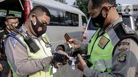 Polisi mengumpulkan kunci kendaraan travel gelap yang disita jajaran Direktorat Lalu Lintas Polda Metro Jaya, Jakarta, Kamis (29/4/2021). Sebanyak 115 kendaraan travel gelap diamankan karena diduga kuat mengangkut pemudik di tengah masa pengetatan larangan mudik 2021. (Liputan6.com/Faizal Fanani)