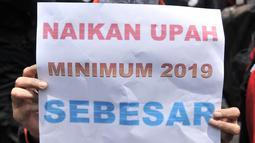 Seorang buruh membawa poster berisi tuntutan kenaikan upah sebesar 30 persen saat menggelar unjuk rasa di depan Gedung Ketenagakerjaan, Jakarta, Rabu (24/10). (Merdeka.com/Iqbal S. Nugroho)