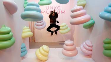 Seorang pengunjung melompat saat berpose di belakang pajangan yang dipamerkan di Museum Unko di Yokohama, Jepang pada Rabu (17/4). Unko Museum alias museum kotoran ini dibuka 15 Maret 2019, periode di mana turis internasional mulai berbondong-bondong berwisata ke Jepang. (REUTERS/Kim Kyung-hoon)