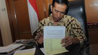 Jokowi menandatangi sejumlah surat dan berkas di ruang kerjanya di Balai Kota, Jakarta, Rabu (17/9/14). (Liputan6.com/Herman Zakharia)