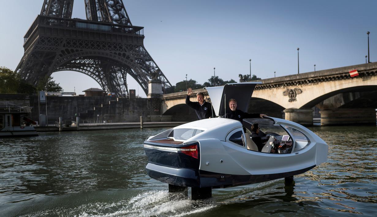 """Pendiri Sea Bubbles Alain Thebault (kiri) dan Anders Bringdal (kanan) berdiri di atas kapal """"flying taxi"""" Sea Bubble saat demonstrasi di sungai Seine di Paris, Prancis (20/5). (AFP Photo/Lionel Bonaventure)"""
