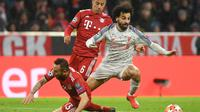 Aksi Mohammed Salah lewati Rafinha pada leg kedua, babak 16 besar Liga Champions yang berlangsung di Stadion Allianz Arena, Munchen, Kamis (14/3). Liverpool menang 3-1. (AFP/ Christof Stache)
