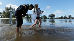 Dua remaja mencari ikan saat banjir melanda Kota Forbes, kawasan pedalaman di New South Wales, Australia, Selasa (27/9). Sungai Lachlan meluap karena tak sanggup menampung air yang berlimpah akibat hujan deras. (REUTERS / Jason Reed)